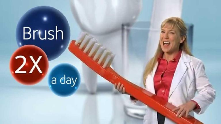 Lady holding a large toothbrush next to over-sized teeth.